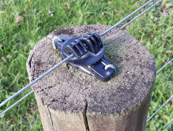 Electric wire on top of fence post